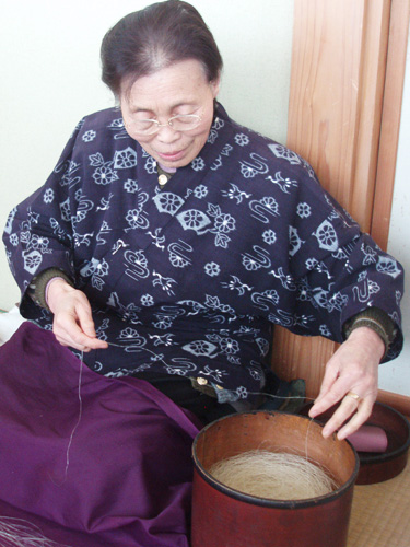 【 苧績み(おうみ)】 口に含みやわらかくした苧麻を爪で細く裂き、繋ぎ合わせて糸にします。 写真は伝統工芸士・荒川セツ子さん。