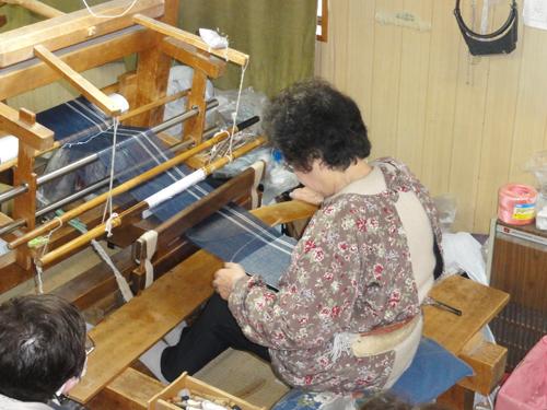 経糸を腰で引いて張り、杼(ひ)という道具を用いて緯糸を打ち込んでいきます。