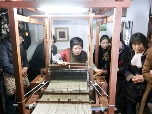 高機による作業風景。 出来上がった糸の経糸を織機に通し、織っていきます。